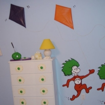 Another view including the painting, kites, green eggs and ham sculpture and dresser.